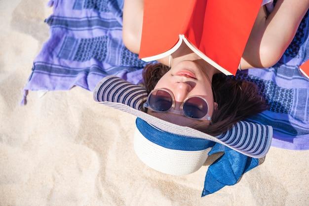 Primo piano della donna graziosa che si trova e che legge un libro sulla spiaggia tropicale nell'ora legale.