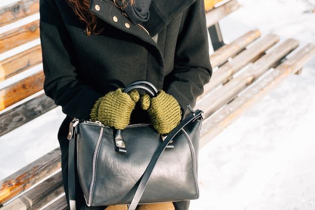 Primo piano della donna in cappotto e guanti con una borsa che si siede su un banco
