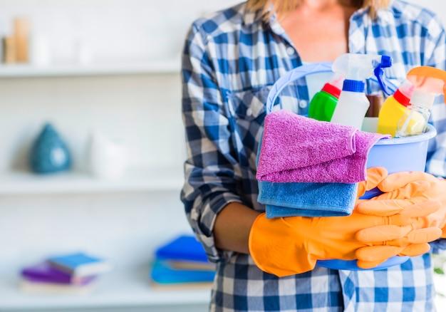 Primo piano della donna in guanti di gomma che tengono secchio delle attrezzature per la pulizia
