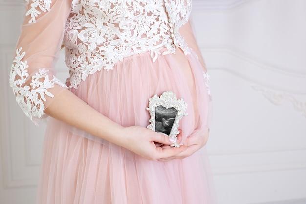 Primo piano della donna incinta che tiene un'ecografia sulla sua pancia. la donna incinta gode della prima foto del suo bambino non ancora nato nella cornice