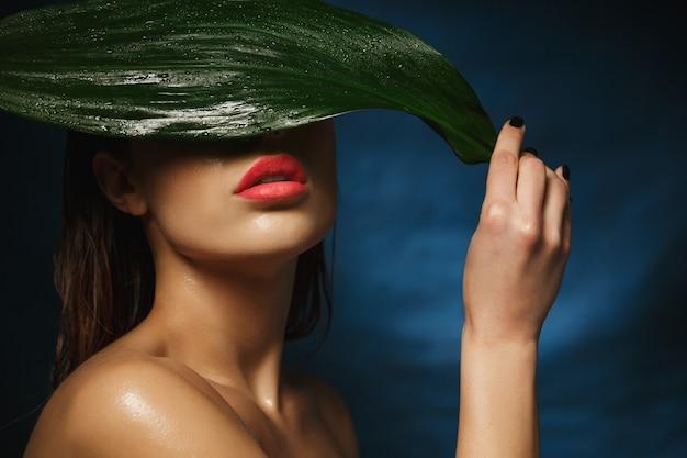 Primo piano della donna nuda adatta che si nasconde sotto la grande foglia bagnata.