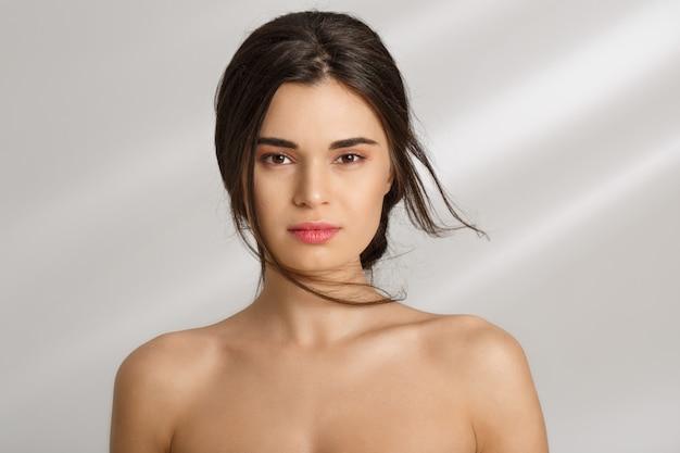Primo piano della donna nuda che sembra straigt. isolato su muro grigio