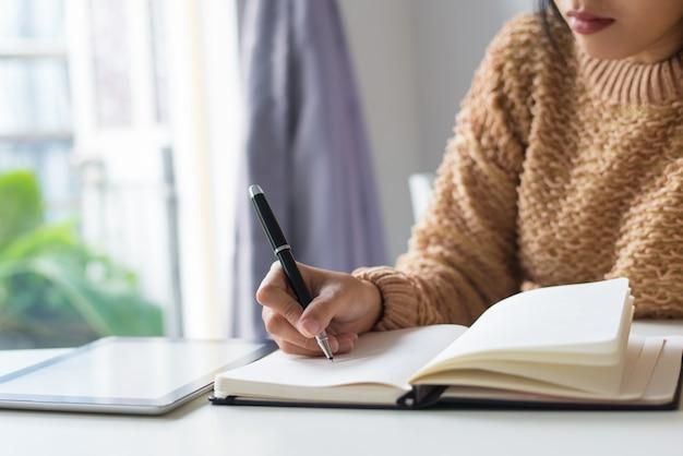 Primo piano della donna pensierosa che scrive le idee in diario