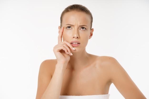 Primo piano della donna preoccupata che esamina brufolo sul fronte