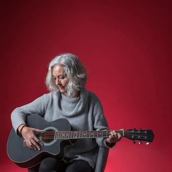 Primo piano della donna senior che si siede nella sedia che gioca la chitarra contro il fondo rosso