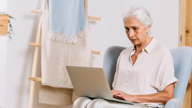 Primo piano della donna senior che si siede sulla sedia facendo uso del computer portatile