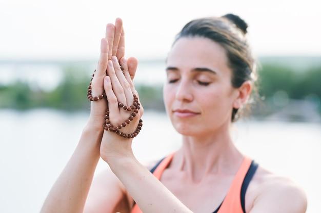 Primo piano della donna serena con gli occhi chiusi che tocca i branelli mentre medita da solo all'aperto