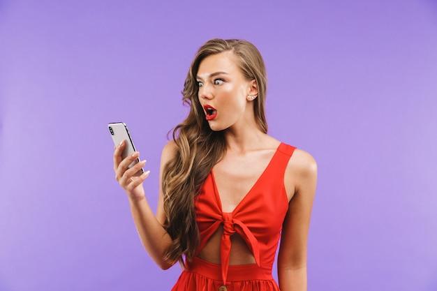 Primo piano della donna sorpresa o colpita che porta vestito rosso che si domanda o che esprime sorpresa mentre tenendo telefono cellulare