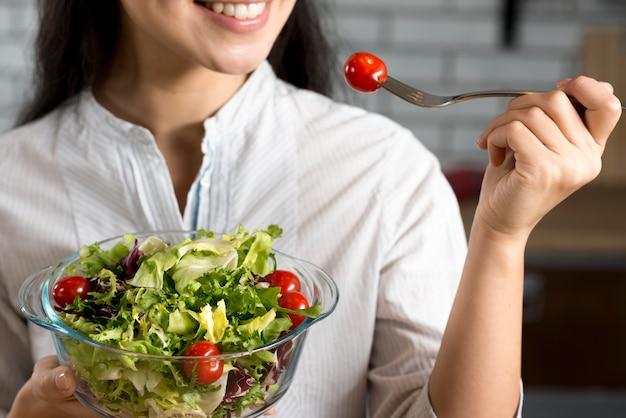 Primo piano della donna sorridente che mangia insalata sana fresca