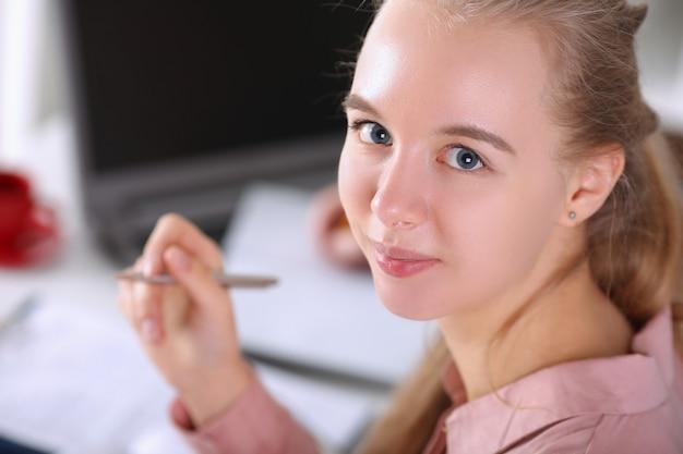Primo piano della donna sorridente dell'assistente che esamina macchina fotografica con letizia. documenti di firma businesslady allegri. bionda in posa in ufficio. concetto di business e società