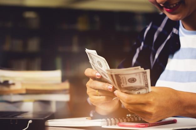 Primo piano della donna, studente contando ci dollari banconote soldi con felice in biblioteca