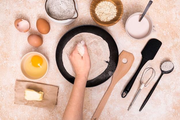 Primo piano della farina della holding della mano con gli ingredienti per la fabbricazione del pane sul contesto strutturato