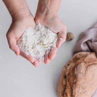 Primo piano della farina di holding della mano di un panettiere