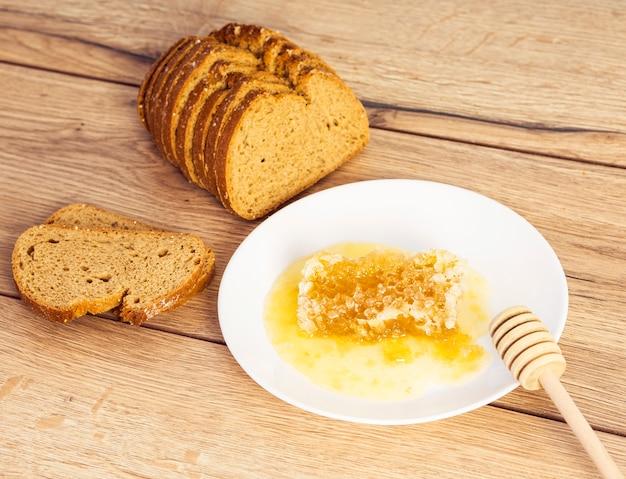 Primo piano della fetta del pane nero con il favo