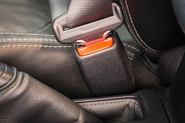 Primo piano della fibbia di una cintura di sicurezza o cintura di sicurezza per la guida e il trasporto in auto.