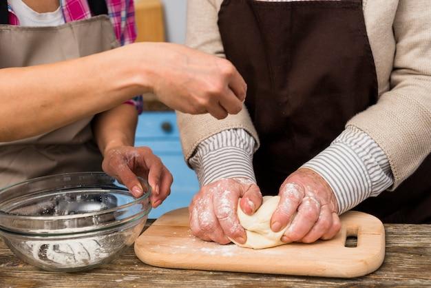 Primo piano della figlia e sua madre che preparano la pasta