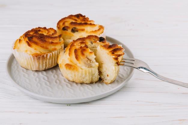 Primo piano della forcella nel cupcake sul piatto sopra il contesto in legno