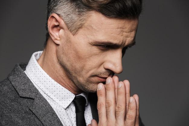 Primo piano della foto dell'uomo calmo premuroso che indossa costume classico e cravatta che tengono le palme insieme nella posa pregante, isolato sopra la parete grigia