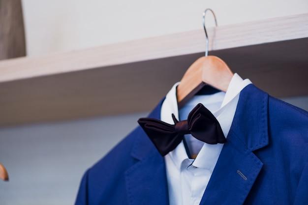 Primo piano della giacca blu con farfallino su un gancio.