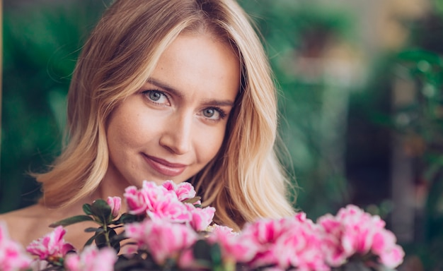 Primo piano della giovane donna bionda sorridente con i fiori rosa che esamina macchina fotografica