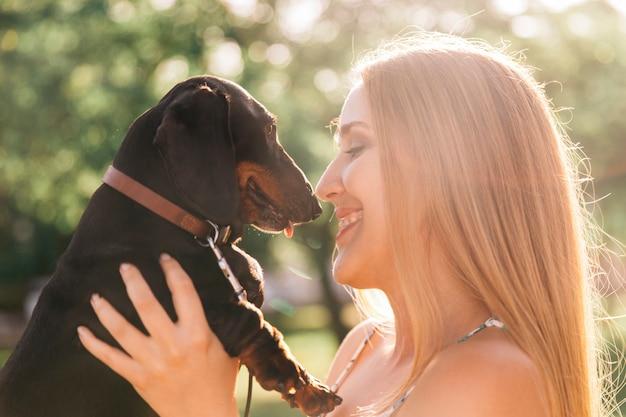 Primo piano della giovane donna che ama il suo cane carino