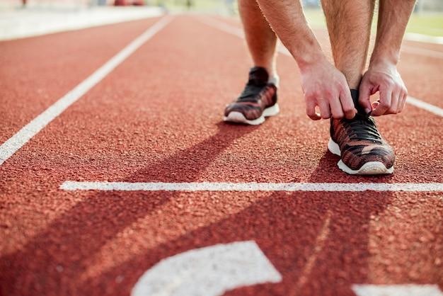 Primo piano della giovane donna che lega la scarpa di sport sulla pista di corsa rossa