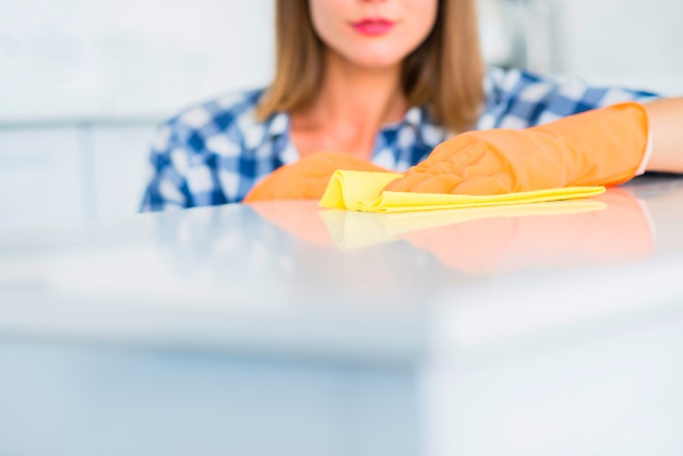 Primo piano della giovane donna che pulisce la superficie bianca con lo spolveratore giallo