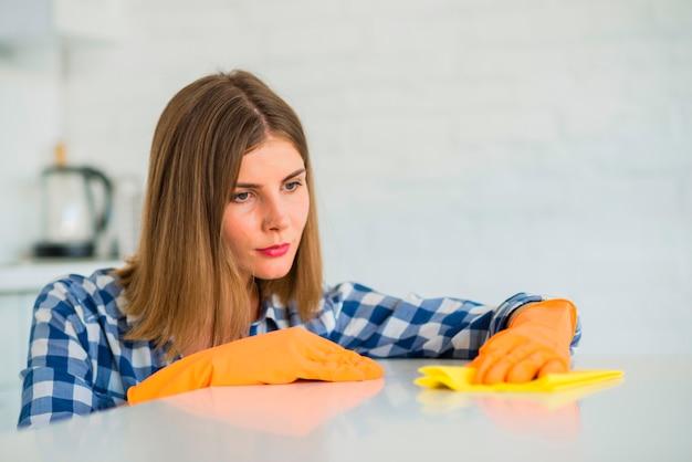 Primo piano della giovane donna che pulisce scrittorio bianco con il tovagliolo giallo