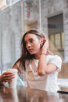Primo piano della giovane donna che si siede in caffè che tiene la tazza di caffè a disposizione