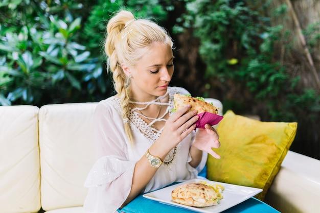 Primo piano della giovane donna che si siede sul sofà che mangia panino all'aperto