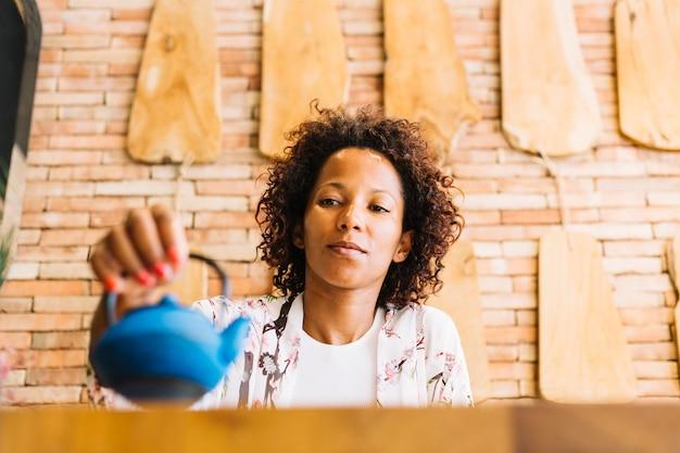 Primo piano della giovane donna che tiene bollitore blu a disposizione