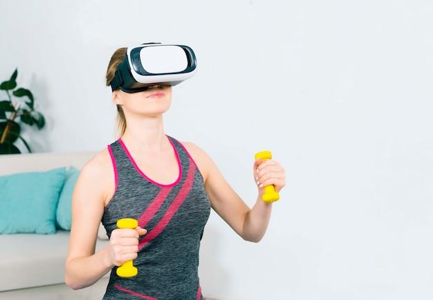 Primo piano della giovane donna che usando la cuffia avricolare di realtà virtuale che si esercita con i dumbbells gialli