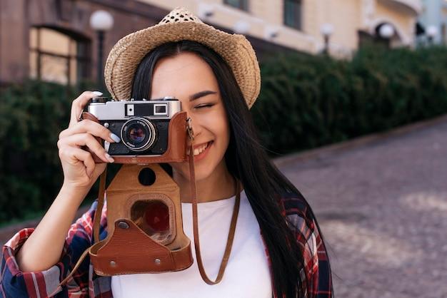 Primo piano della giovane donna felice che prende foto con la macchina fotografica ad all'aperto