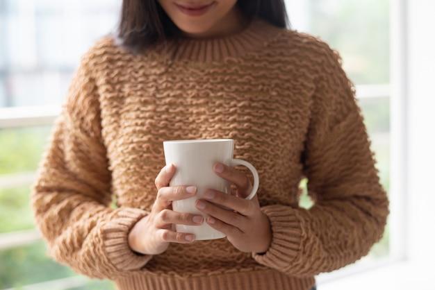 Primo piano della giovane donna nel posto accogliente che tiene tazza bianca