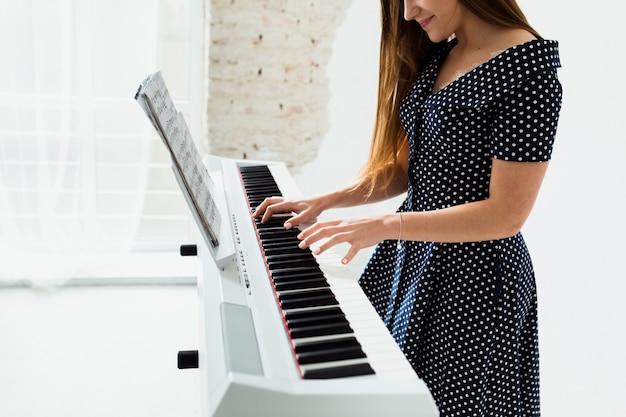 Primo piano della giovane donna sorridente che gioca il piano