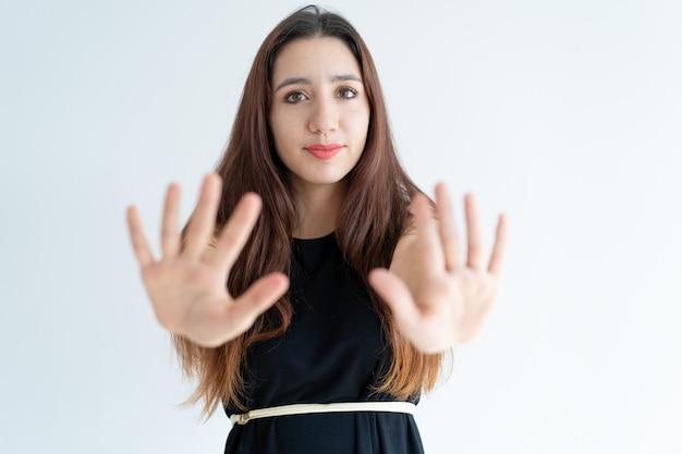 Primo piano della giovane donna sorridente che mostra gesto di arresto