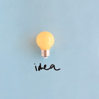 Primo piano della lampadina della luce gialla con la parola di idea su fondo blu