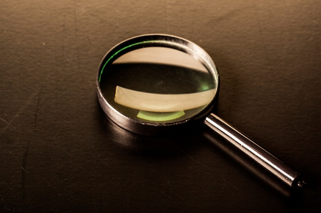 Primo piano della lente d'ingrandimento su superficie scura