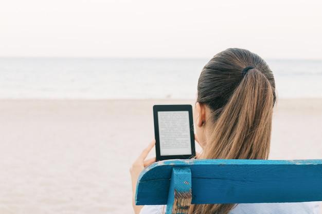 Primo piano della lettura del brunette un libro sulla spiaggia, vista dalla parte posteriore