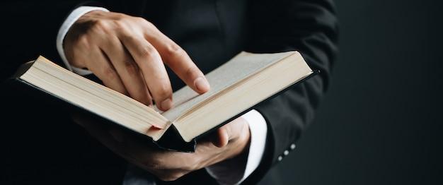 Primo piano della lettura del dito dell'uomo che indica testo in libro.