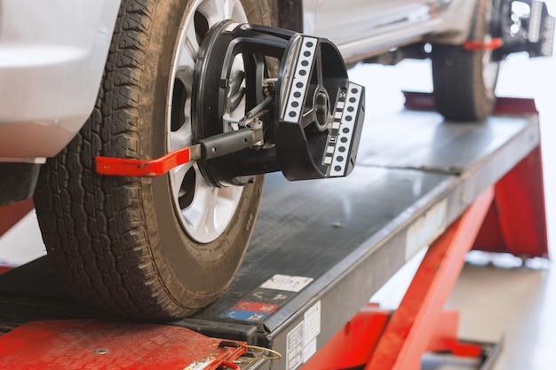Primo piano della macchina d'equilibratura della ruota al centro di servizio della gomma