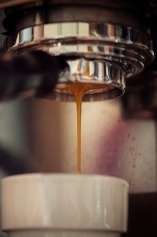 Primo piano della macchina del caffè che produce bevanda del caffè espresso