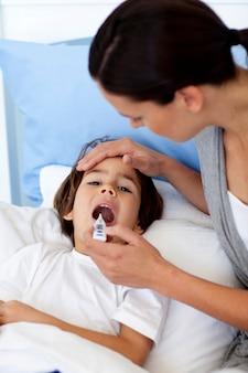 Primo piano della madre che prende la temperatura di suo figlio con un termometro