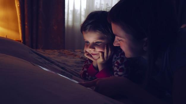 Primo piano della madre e della compressa di sorveglianza della sua piccola figlia a casa.