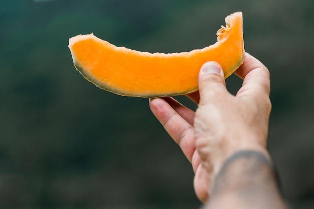Primo piano della mano che dà fetta di muschio melone