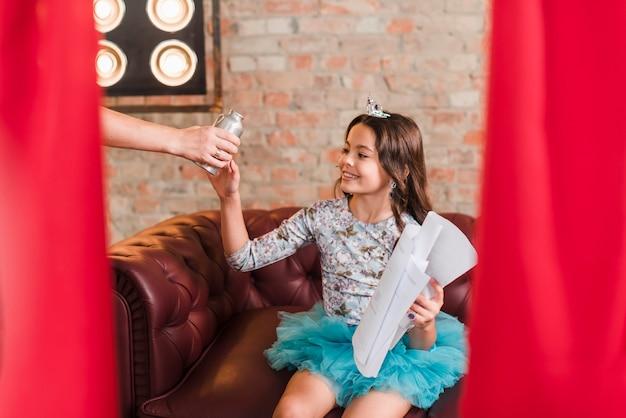 Primo piano della mano che dà la bottiglia di acqua alla ragazza che si siede sugli scritti della holding del sofà