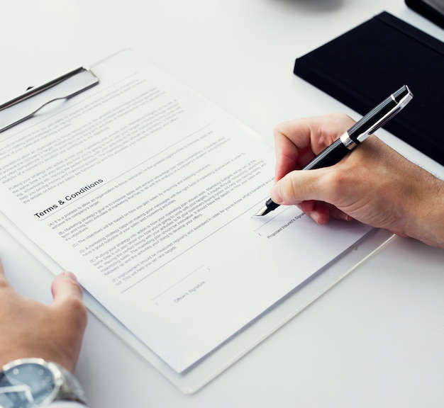 Primo piano della mano che firma l'area di lavoro della carta