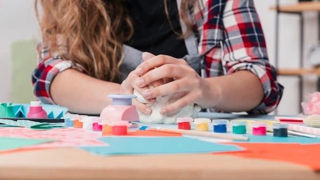 Primo piano della mano che impastano argilla bianca per il mestiere creativo