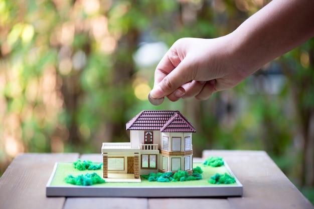 Primo piano della mano che inserisce moneta nella casa di modello sulla tavola di legno