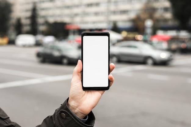 Primo piano della mano che mostra esposizione dello smart phone sulla strada